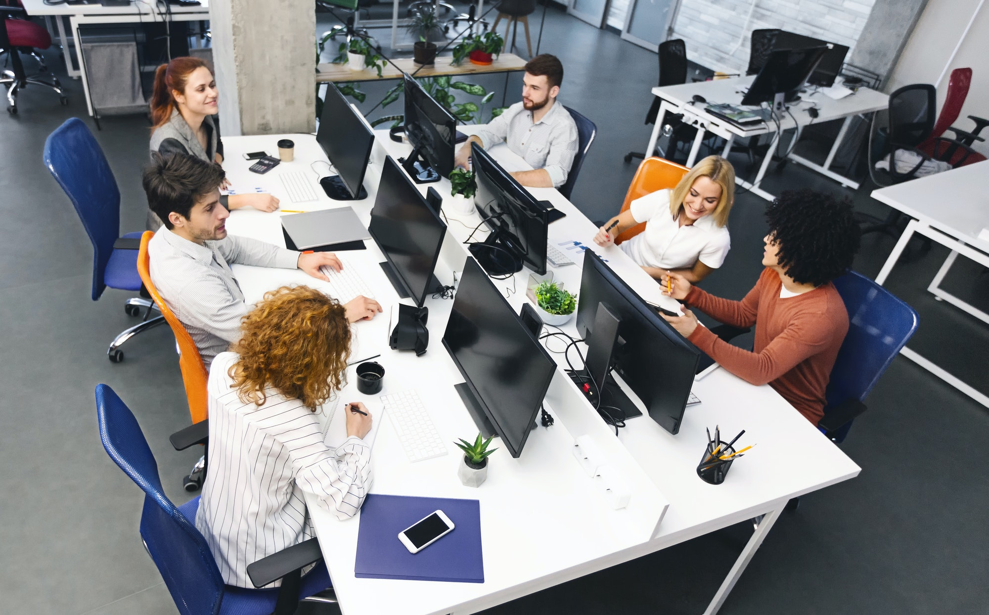 Group of young diverse people discussing project at workplace